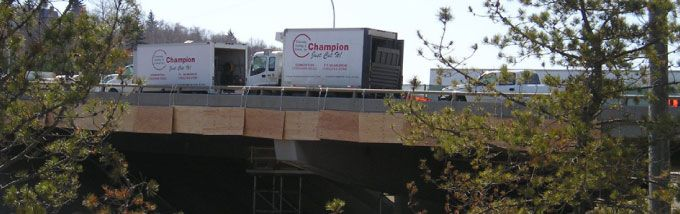 Champion Concrete Cutting Inc. trucks on bridge